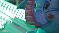 Toy elephant rides on a merry-go-round carousel in Amusement Park at night Stock Footage