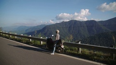 Young woman on scooter mountain road nice view enjoys the freedom of travel Stock Footage