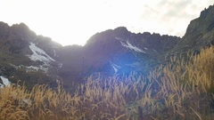 Yellow autumn grass swaying in wind, snow tops with a beautiful lens flare Stock Footage