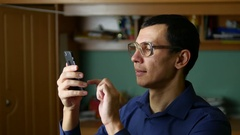 Man glasses spectacled typing message on the phone smartphone social media Stock Footage