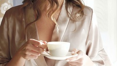 Pretty girl in nighty drinks a cup of coffee near the window. Slowly Stock Footage