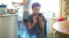 Girl in the kitchen playing smartphone rear mother preparing breakfast Stock Footage