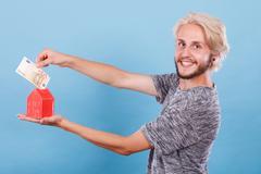 Man puts money into house piggybank Stock Photos