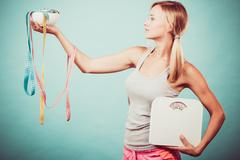 Girl with scales measuring tapes. Weight loss. Kuvituskuvat