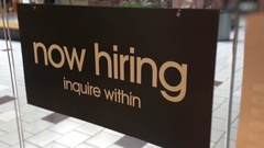 Now hiring sign on glass wall posted in shopping mall store Stock Footage