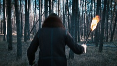 The guy goes through the forest with a torch Stock Footage