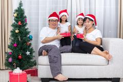 Happy Asian Chinese family exchange Christmas gift at home Stock Photos
