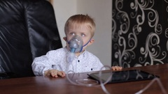 Small boy does therapeutic inhalation using a nebulizer. Stock Footage