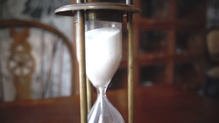 Close up vintage sand clock on wooden table, HD slow motion Stock Footage