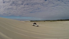4x4 Vehicle driving down a long sand dune Stock Footage