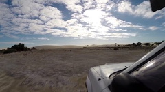 4x4 Vehicle driving offroad torwards sand dunes Stock Footage