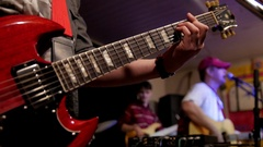 Man playing red electric guitar at rock concert, stage lighting Stock Footage