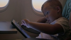 Close up view of small boy playing with touch pad on the table in aircraft Stock Footage