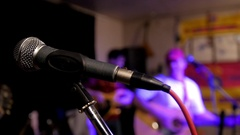 Microphone. Rock band playing musical instrument at concert Stock Footage