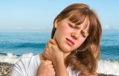 Woman having pain in her neck on a beach near the Black sea Kuvituskuvat