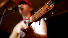 Rock artist in red cap in the garage playing guitar and sing in microphone Stock Footage