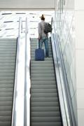 Man standing on escalator with travel bags Stock Photos