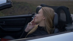 Young girl smoking in a convertible Stock Footage