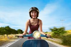 Attractive asian woman riding a blue scooter Stock Photos