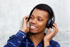 Smiling young black man with headphones listening to music Stock Photos