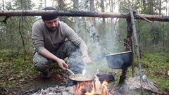 Hunter man cooks food from the fire Arkistovideo