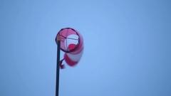 Storm brewing wind sock flapping in strong wind dark overcast Stock Footage