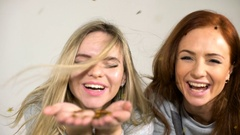 Two young girls throw confetti on a white background Stock Footage