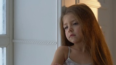 Winter Day. Girl looking out the window at the falling snow Stock Footage
