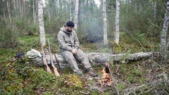 Hunter man at a fire in the forest Arkistovideo
