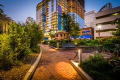 Walkway and modern buildings at twilight, seen at Romare Bearden Park, in U.. Stock Photos