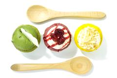Three cupcake flavor green red and yellow color with spoon on top view Stock Photos