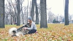 Image of young girl playing with her dog, alaskan malamute Stock Footage