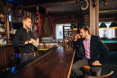 Young man talking to a bartender in the bar Stock Photos