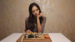 Young beautiful woman inspects the desk full of sushi and rejects to eat it Stock Footage