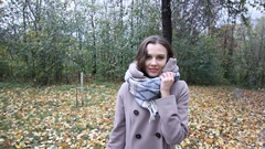 Smiling young attractive woman with the colored leaf in her hand during the fall Stock Footage
