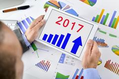 Man observing an economical forecast for 2017 in his tablet Stock Photos