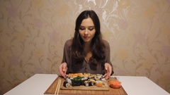 Young woman is taking the desk full of sushi and enjoying it smell Stock Footage