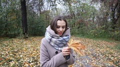 Smiling young attractive woman with the colored leaf in her hand waves in camera Stock Footage