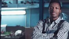 Auto mechanic wearing striped shirt smiles Stock Footage