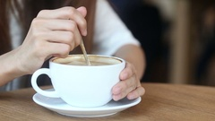 Women stir latte art coffee white up in cafe, Closeup Stock Footage