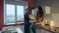 Young unhappy couple at the kitchen. Man washing the dishes while the woman Stock Footage