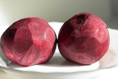 Two peeled beets that lying on the white plate. Stock Photos