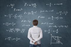 Business person standing in front of mathematical formula. Stock Photos