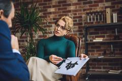 Serious psychologist showing inkblot on paper Stock Photos