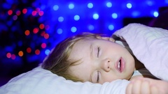 Beautiful baby sleeping on the bed Christmas night. In the background, lights Stock Footage