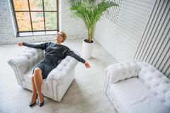 Smiling advisor relaxing on armchair Stock Photos