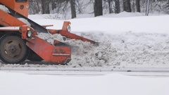 Shovel racks durty snow along road. Сlearing streets of snow using machines Stock Footage