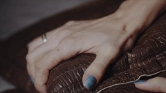 Woman's hands clenching leather pillow because of pain Stock Footage
