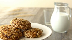 Delicious sweet oatmeal cookies with seeds. Milk-jug and glass, on wooden rustic Stock Footage