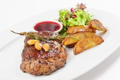 Thick juicy beef steak with potato and salad Stock Photos